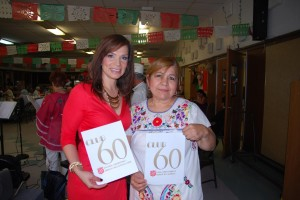 salvation army paola with coordinator holding club 60 sign
